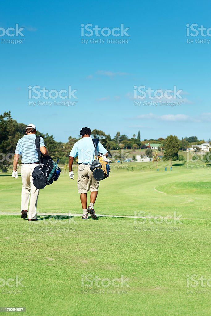 Male golf player walking towards their next hole royalty-free stock photo