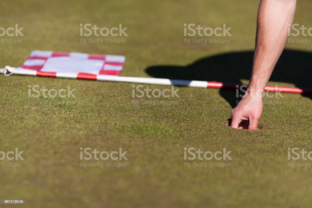 Male golf player putting the golf ball on the ground only his arm is...
