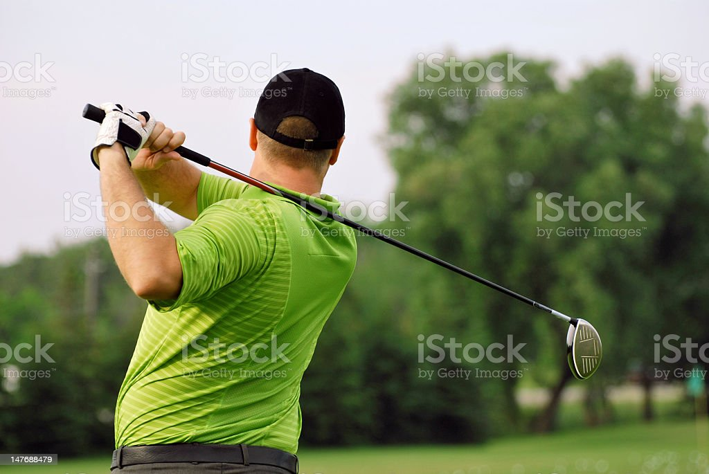 Male golfer in green admiring his long drive post swing stock photo