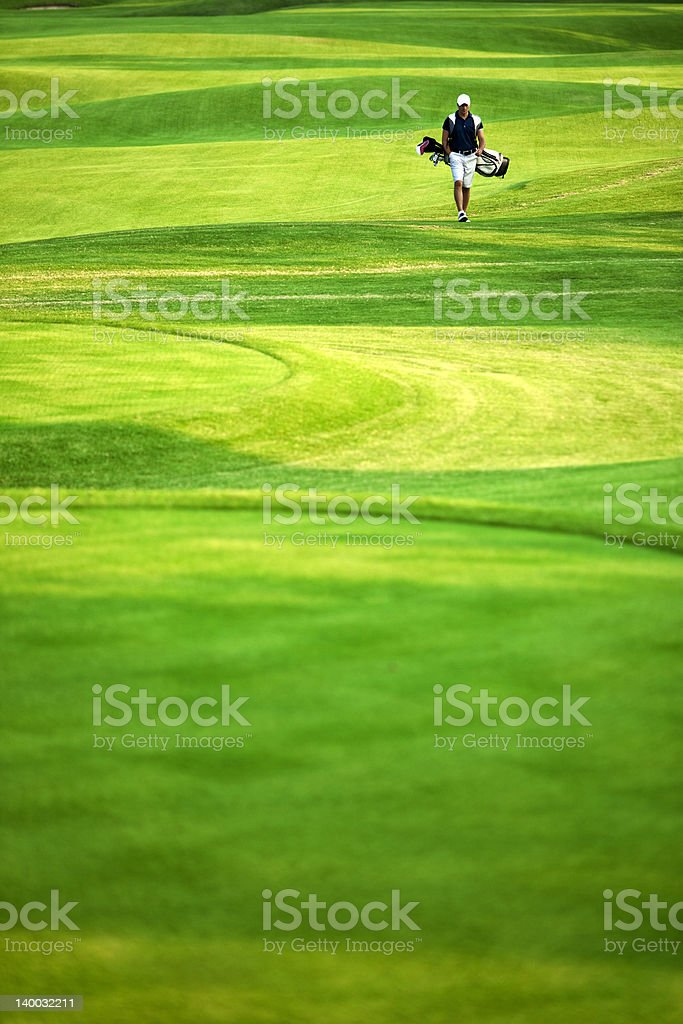 A male golfer in the distance is walking down the fairway royalty-free stock photo