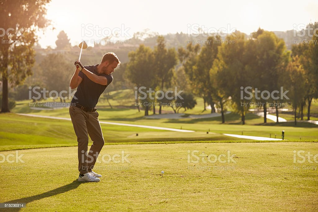 Male Golfer Lining Up Tee Shot On Golf Course stock photo