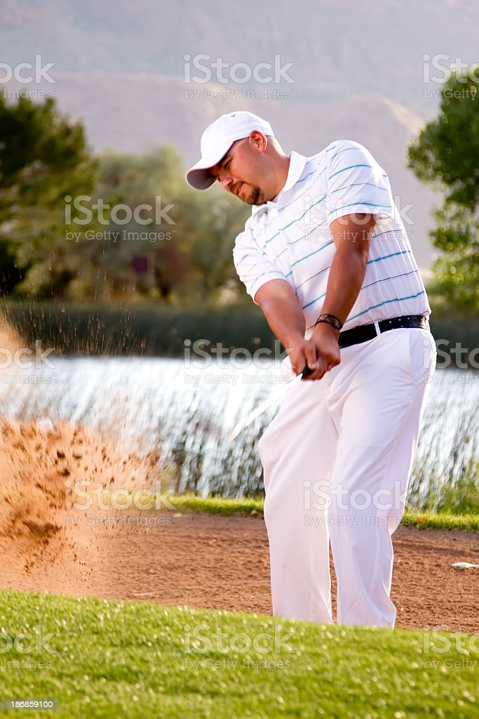 Male Golfer Making Bunker Shot with Sand Wedge royalty-free stock photo