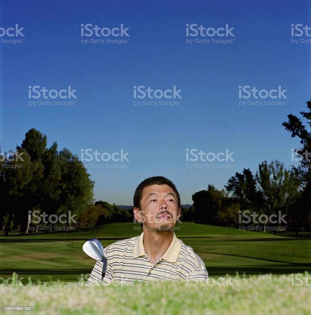 Male golfer peering over bunker edge royalty-free stock photo
