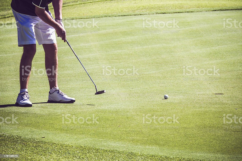 Male golfer putting on green royalty-free stock photo