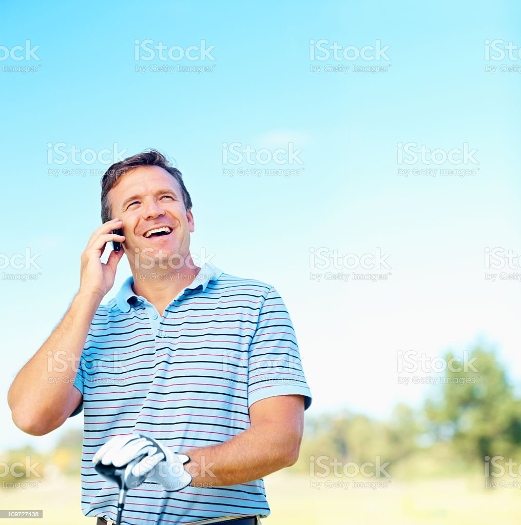 Male golfer stops his game to communicate on his cell phone royalty-free stock photo