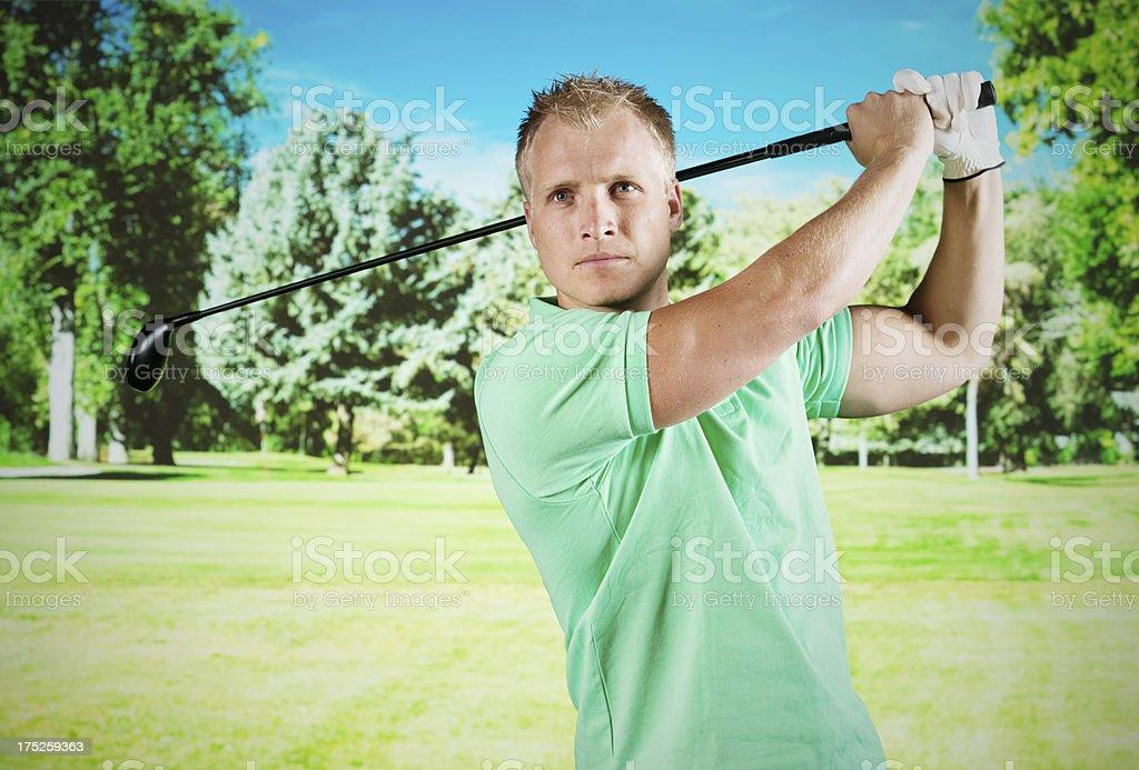 Male golfer swinging a golf club royalty-free stock photo