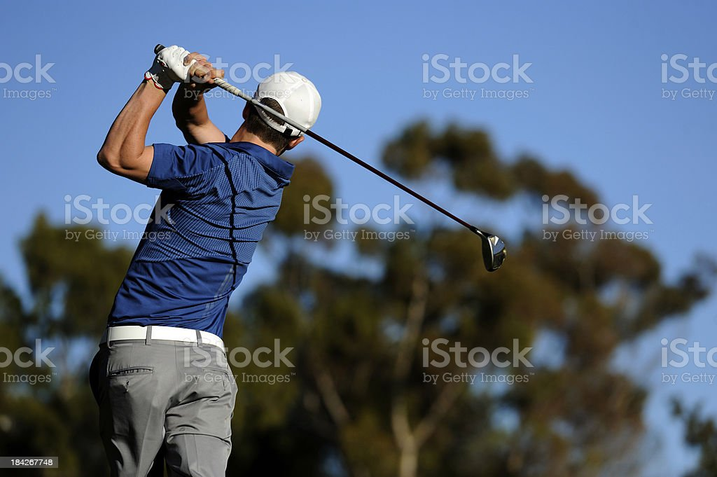 Male golfer swinging his club stock photo