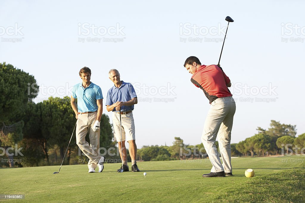 Male golfer swings from tee box stock photo