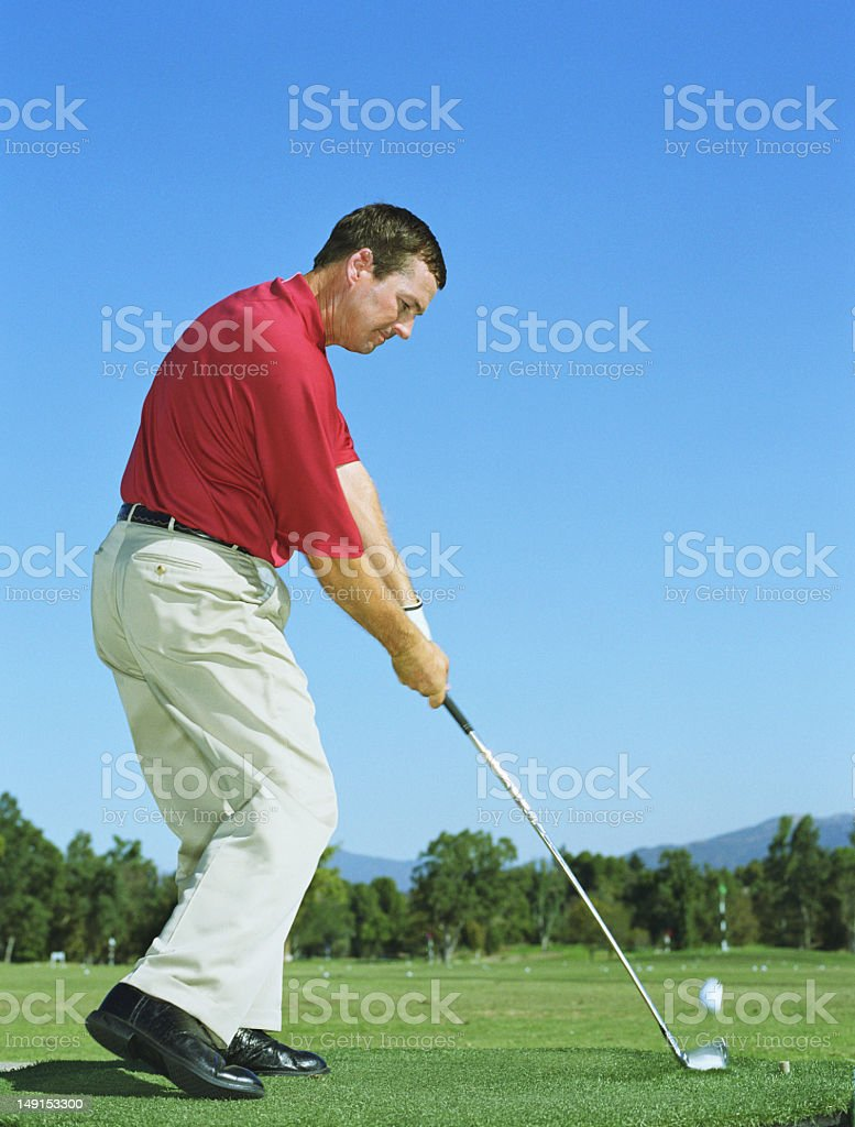 Male golfer taking shot, side view royalty-free stock photo