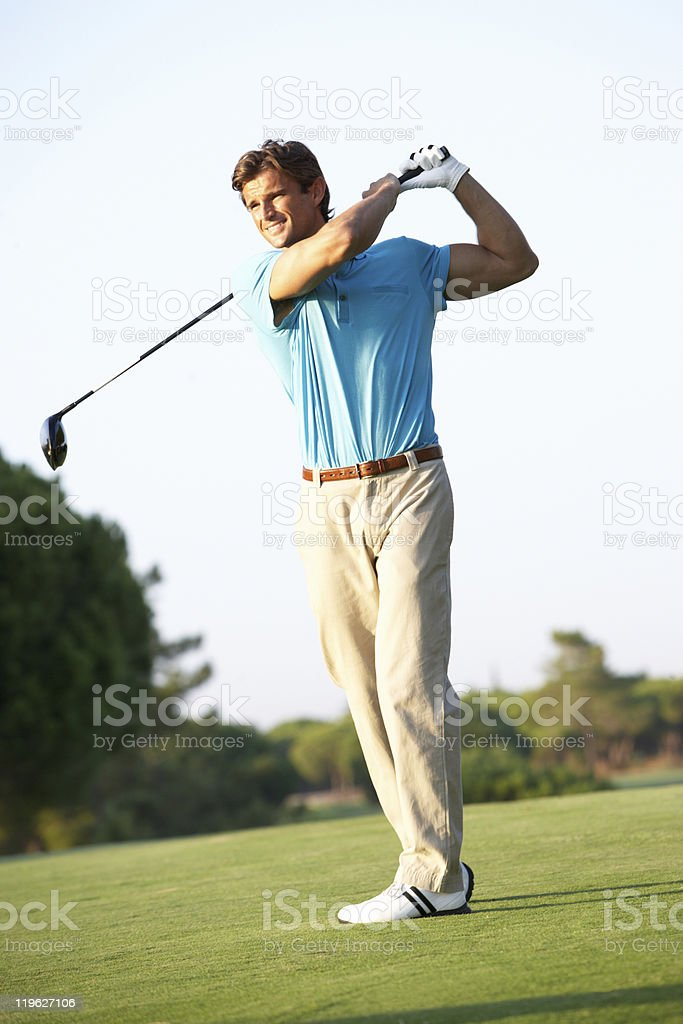 Male Golfer Teeing Off On Golf Course royalty-free stock photo