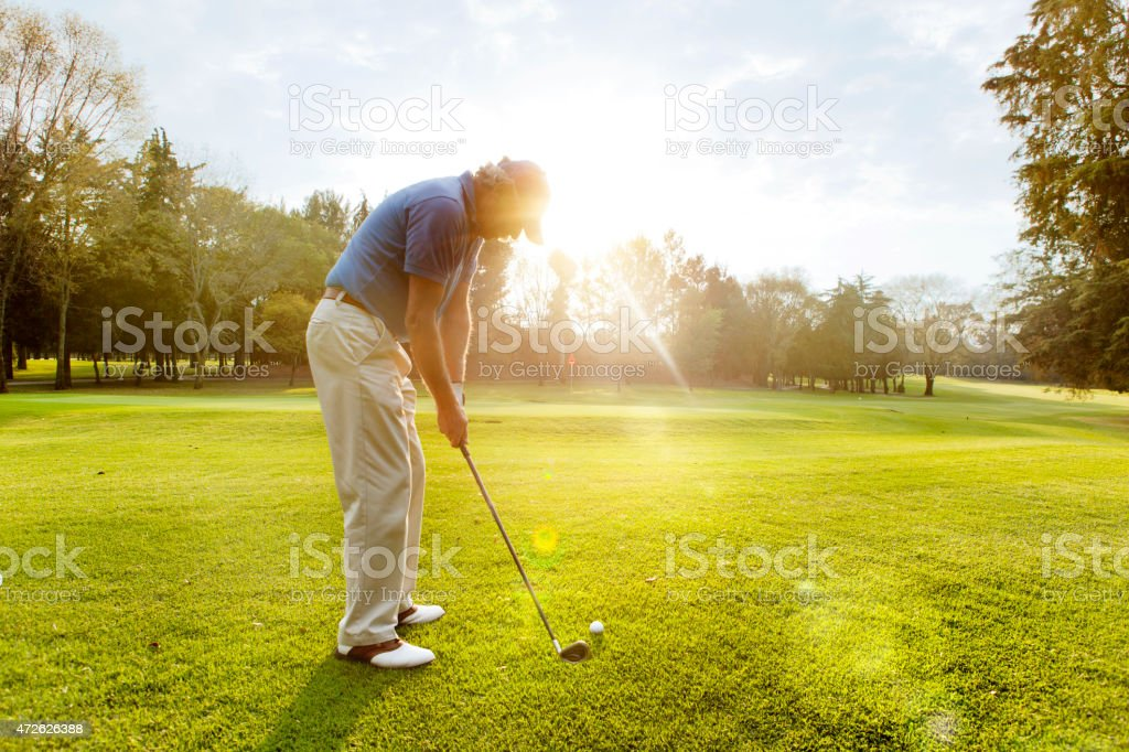 Male golfer teeing off stock photo