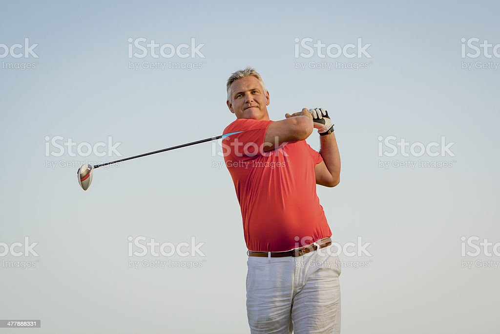 Male golfer teeing off with his driver royalty-free stock photo