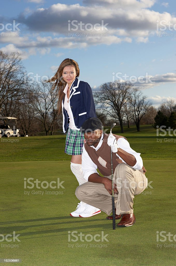 Male golfer with sexy caddy stock photo