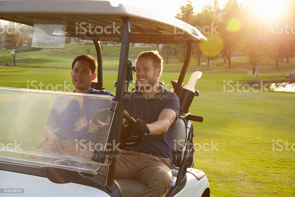 Male Golfers Driving Buggy Along Fairway Of Golf Course stock photo