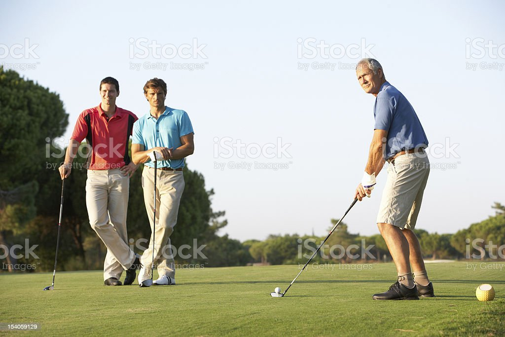 Male Golfers Teeing Off On Golf Course stock photo
