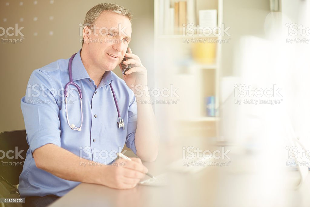 male gp chats on the phone stock photo