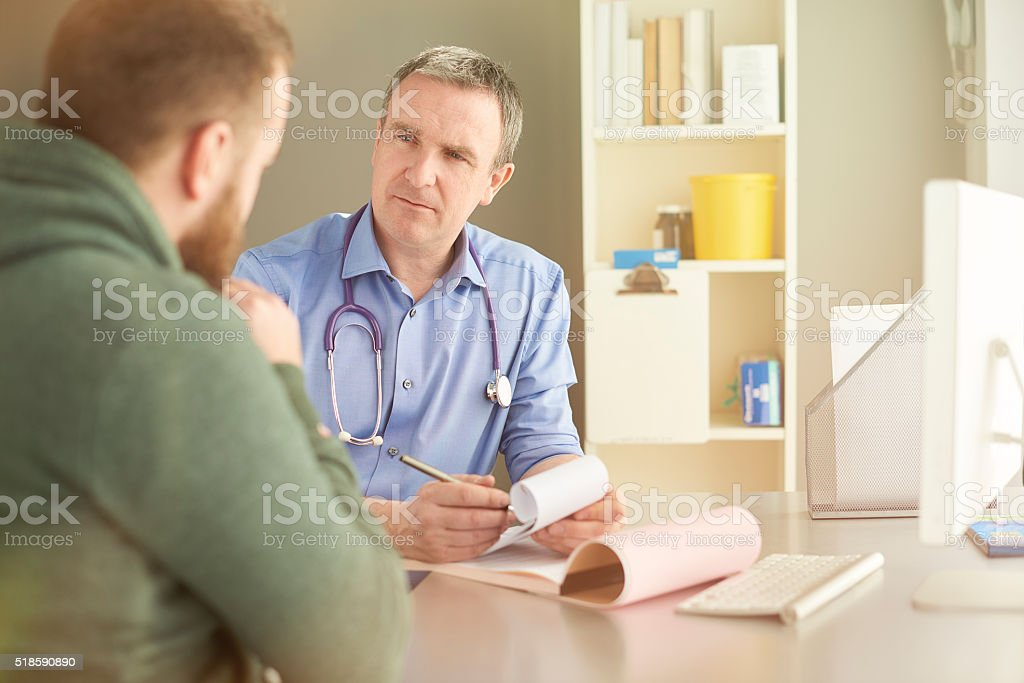 male gp listening to male patient stock photo