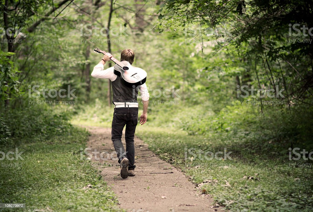 A male guitarist walking on a path royalty-free stock photo