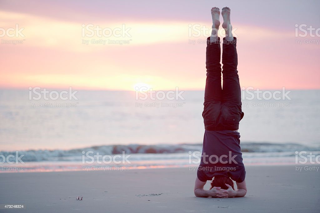 Male guy doing headstand at the beach of St.Peter-Ording, Germany stock photo