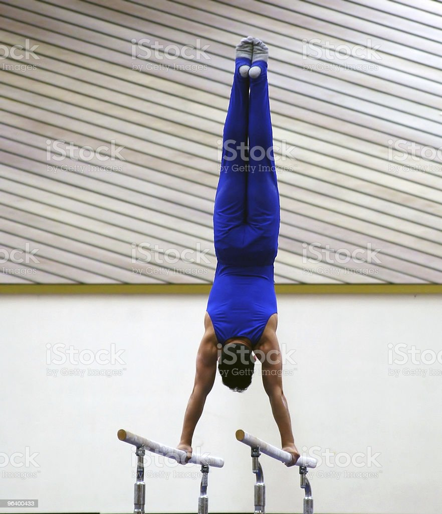 A male gymnast in a blue outfit working the bars at the gym stock photo
