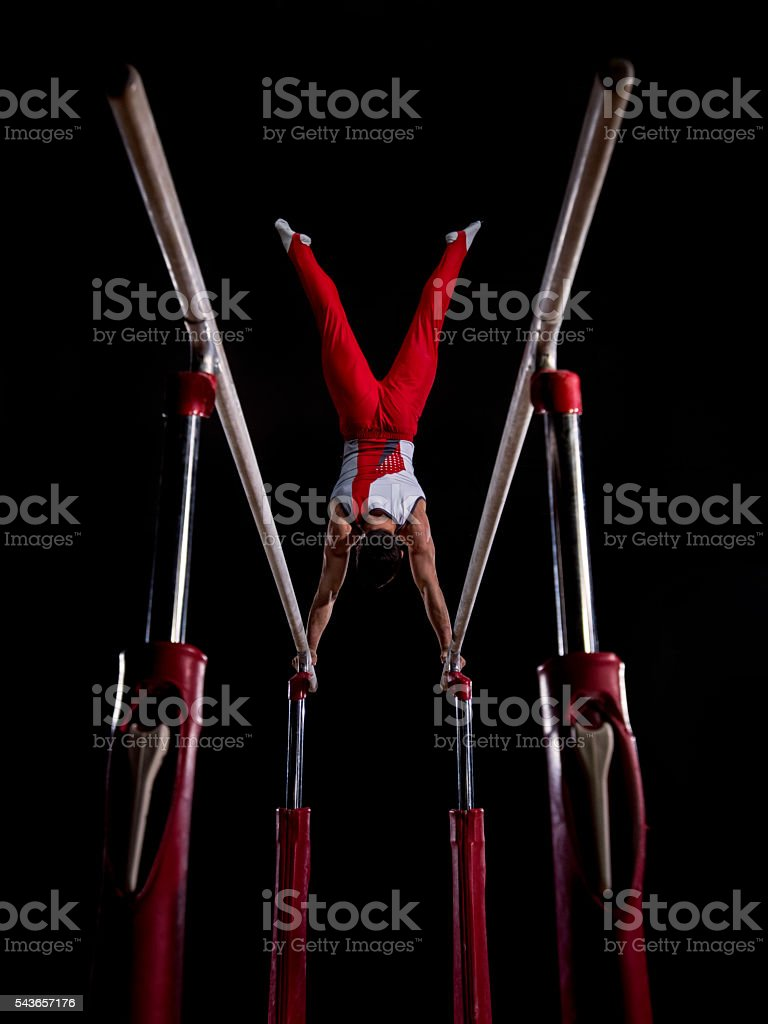 Male gymnast on parallel bars stock photo