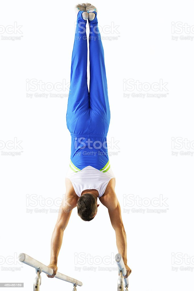 Male gymnast performing handstand on the parallel bars stock photo