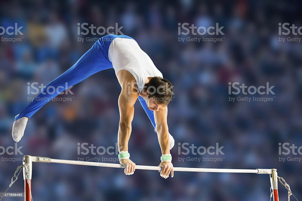Male gymnast performing routine on horizontal bar stock photo