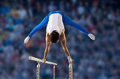 Male gymnast performing routine on parallel bars