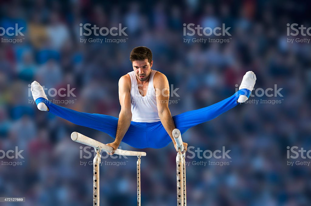 Male gymnast performing routine on parallel bars stock photo