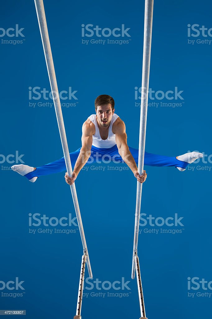 Male gymnast performing routine on the parallel bars stock photo
