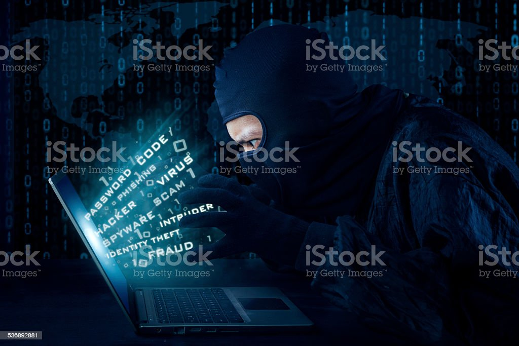 Male hacker with mask stealing information stock photo