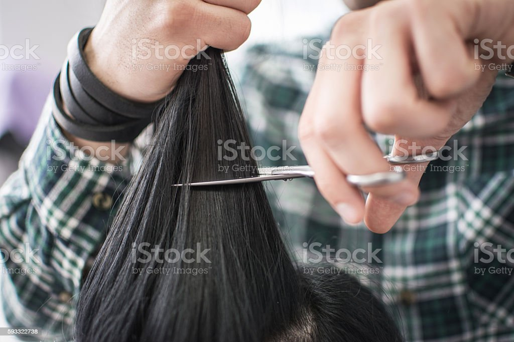 Male hairdresser cutting clients hair with scissors in salon. stock photo