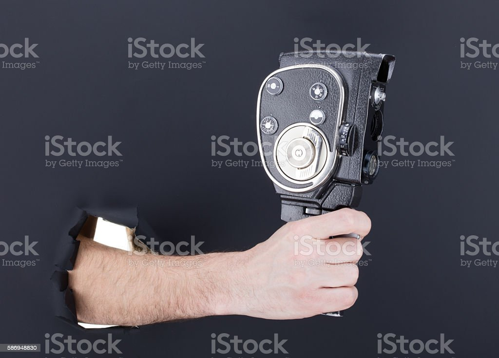 Male hand breaking through the black paper background, stock photo