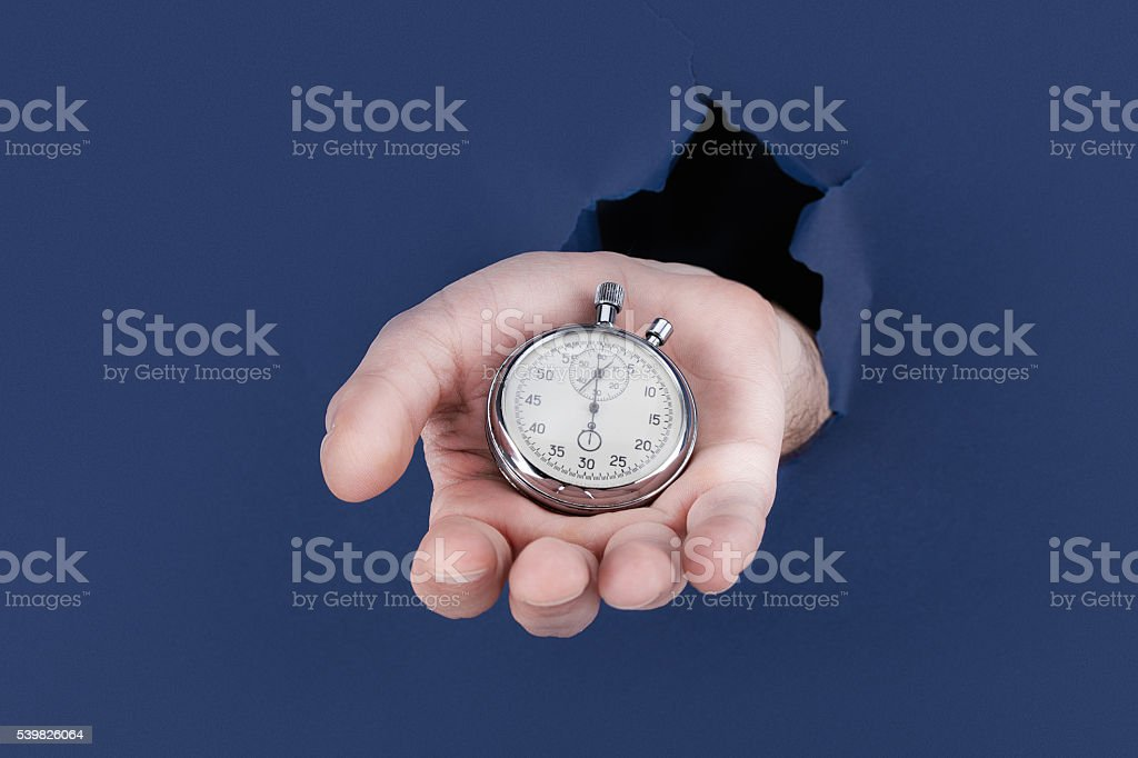Male hand breaking through the blue paper background and stock photo