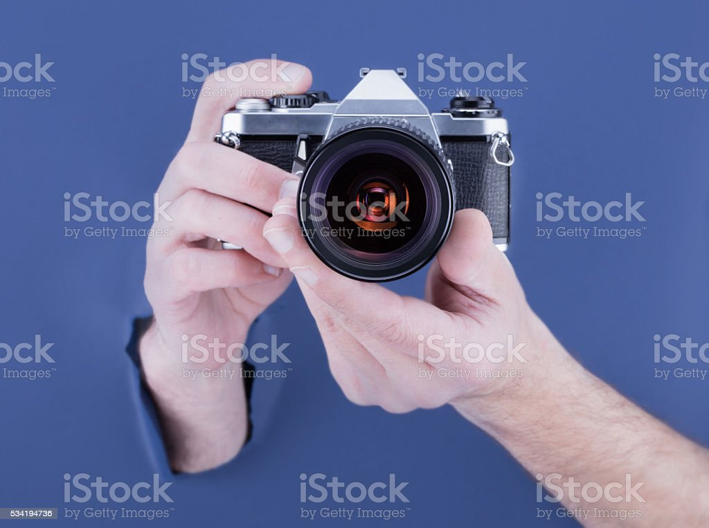 Male hand breaking through the blue paper background  camera stock photo