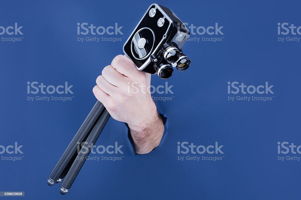 Male hand breaking through the blue paper background stock photo