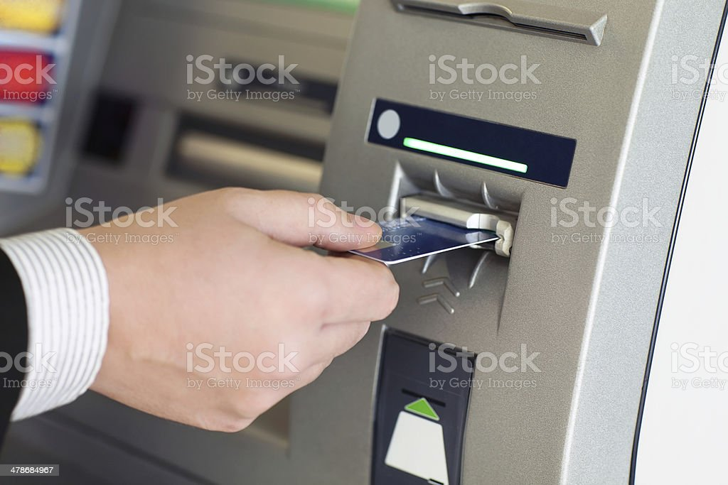 male hand businessman inserts credit card into the ATM stock photo