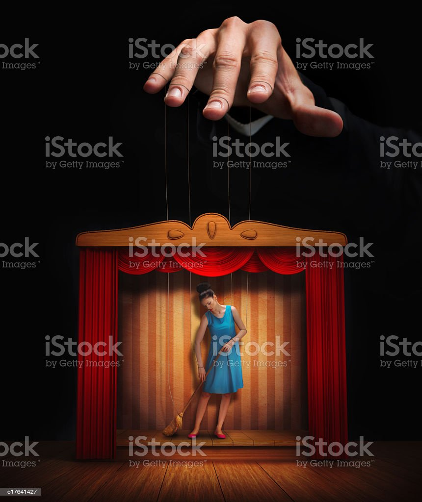Male hand controlling a small woman puppet stock photo