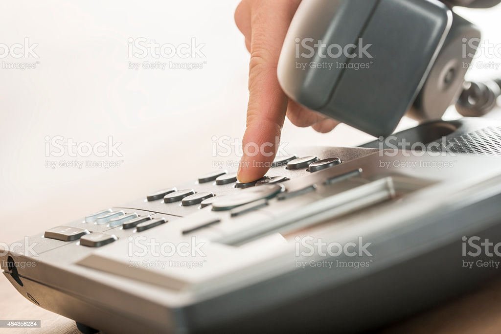 Male hand dialing a classical landline telephone stock photo