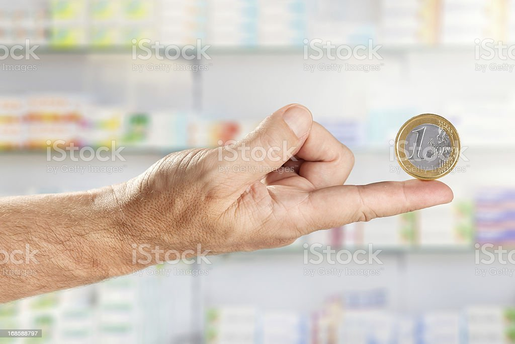 Male hand floating one EURO coin in pharmacy royalty-free stock photo