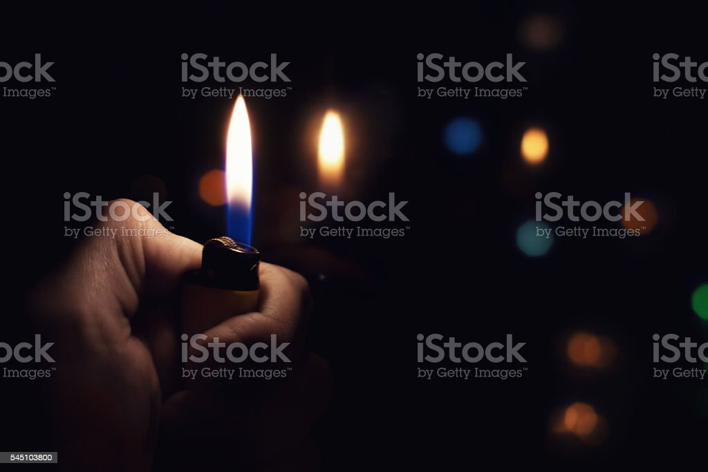 Male hand holding a burning lighter stock photo