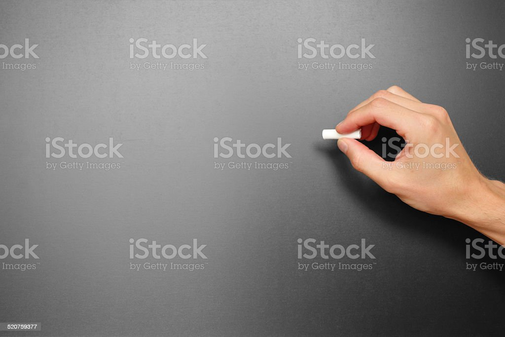 Male hand holding a chalk ready for writing something stock photo