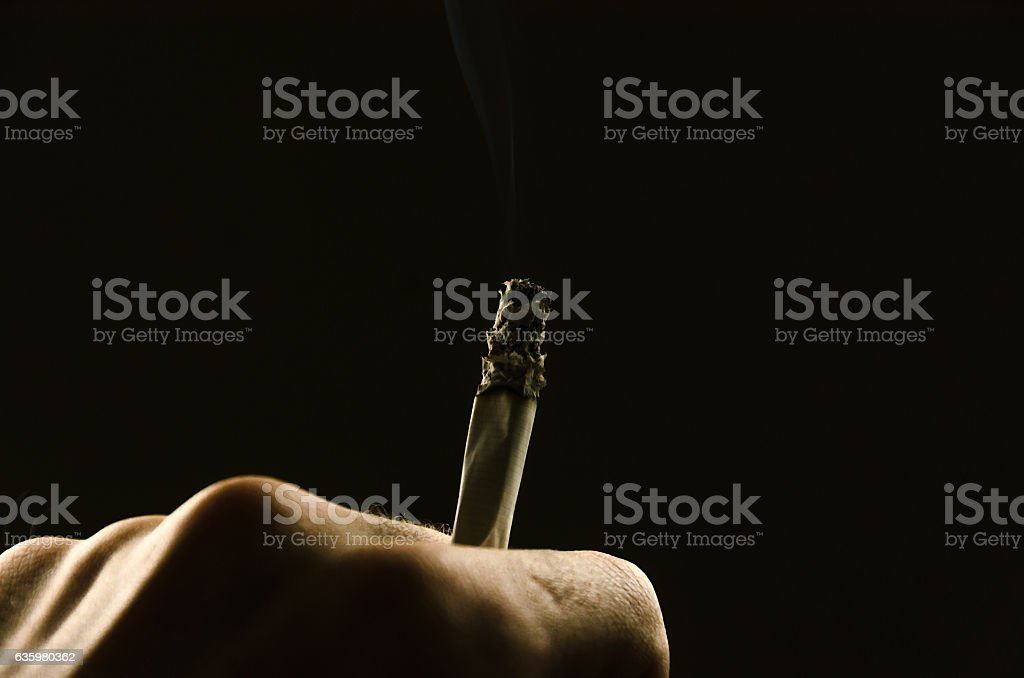 male hand holding a cigarette between his fingers stock photo