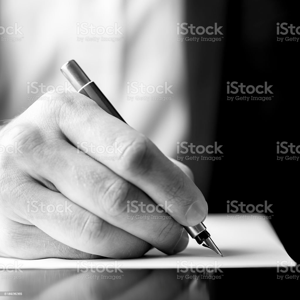 Male hand holding a fountain pen as though writing stock photo