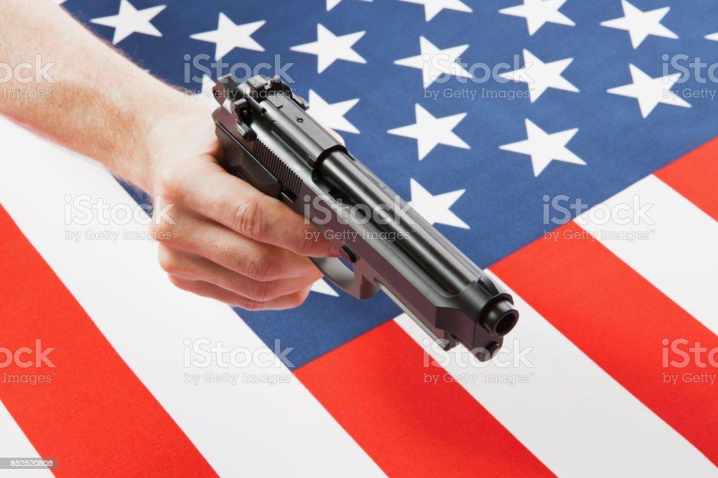 Male hand holding a handgun above satin US flag - studio shoot stock photo