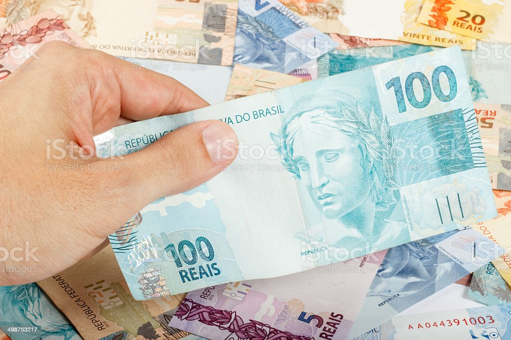 male hand holding a hundred reais, brazilian money stock photo