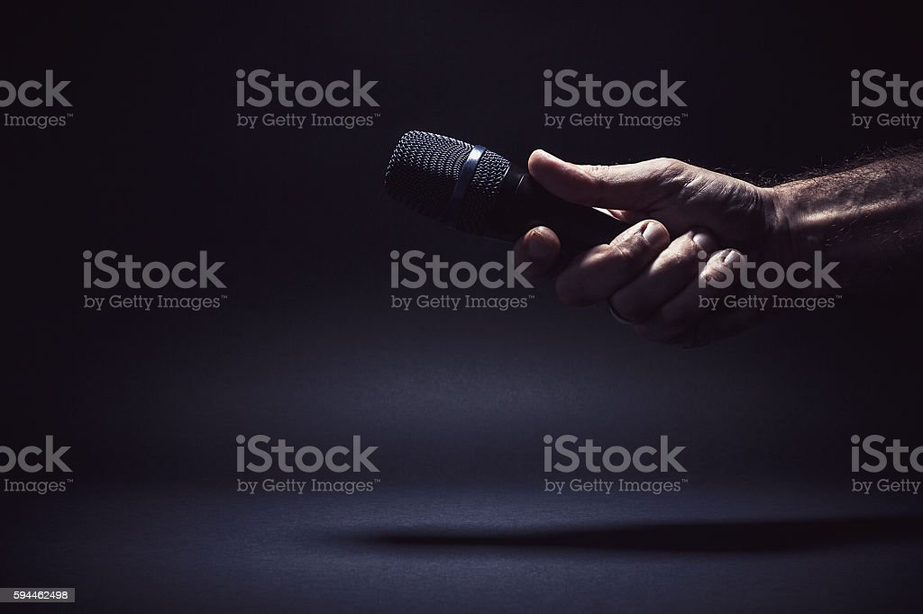 Male Hand Holding a Microphone stock photo