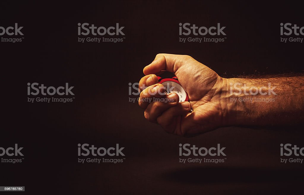 Male Hand Holding a Red Clock stock photo