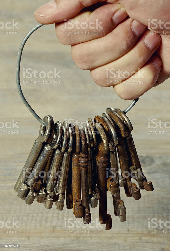 Male hand holding a ring with old keys stock photo