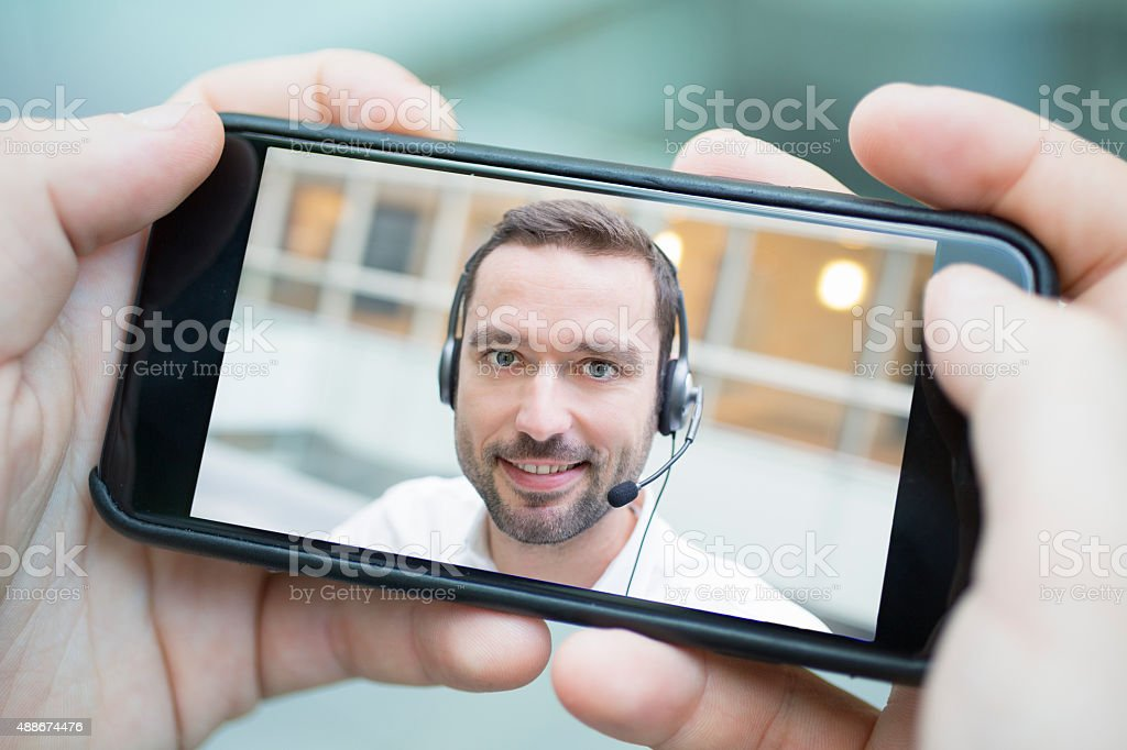 male hand holding a smartphone during a skype video stock photo